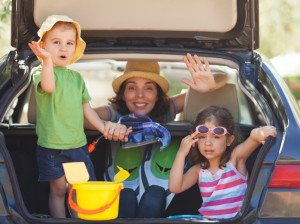 Family sitting in the back of a car smiling to camera and waving.