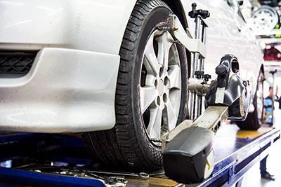 Image of a white car having its alignment adjusted by Active Green + Ross Complete Tire & Auto Centre in Toronto, ON